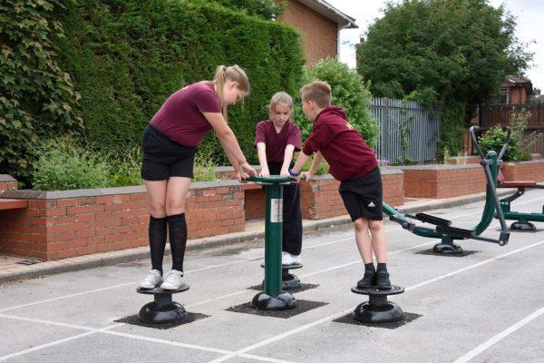 three children using outdoor gym equipment for schools