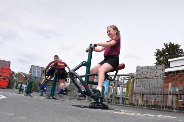 children using outdoor gym equipment for schools