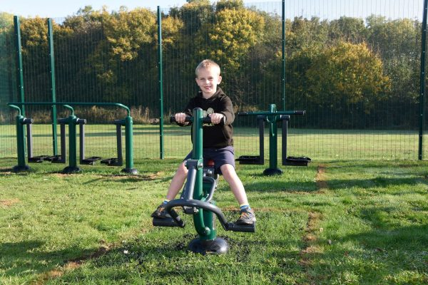 one boy using outdoor gym equipment for schools