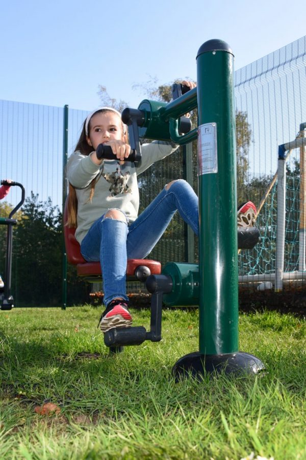 girl using outdoor gym equipment for schools