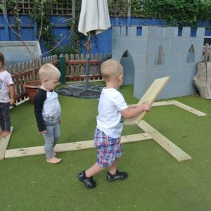 children playing with wooden playground equipment