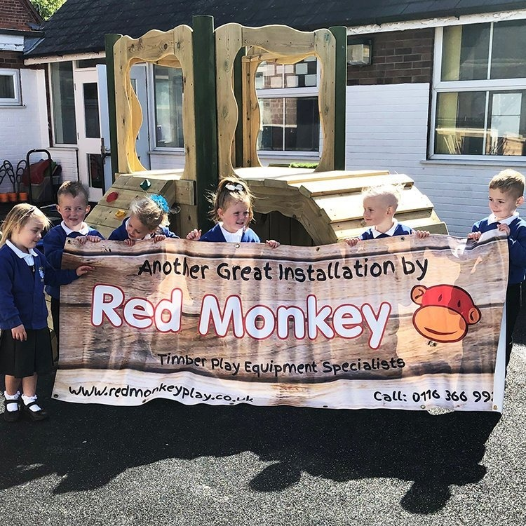 red monkey play playground installation sign being held by students