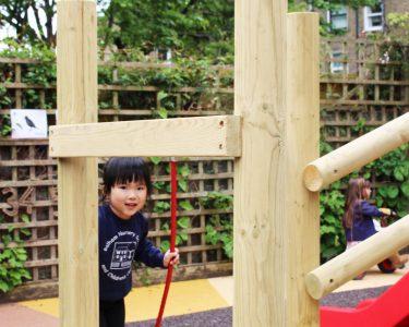 boy climbing wooden climbing frame steps