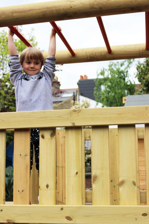 boy hanging from monkey bars on wooden climbing frame