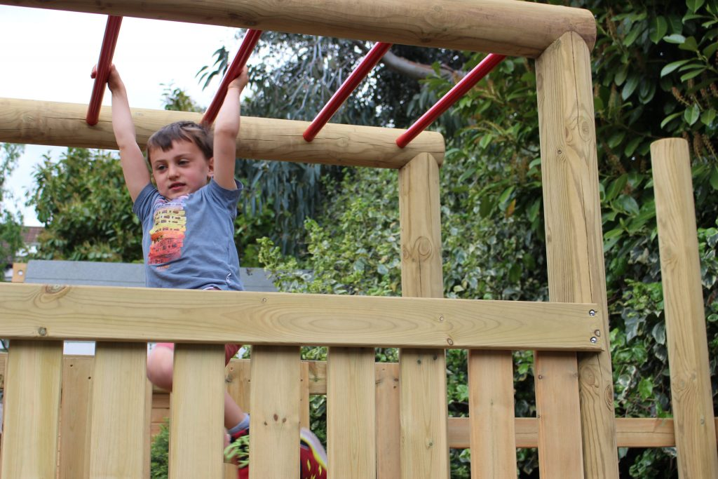 child hanging from climbing frame monkey bars