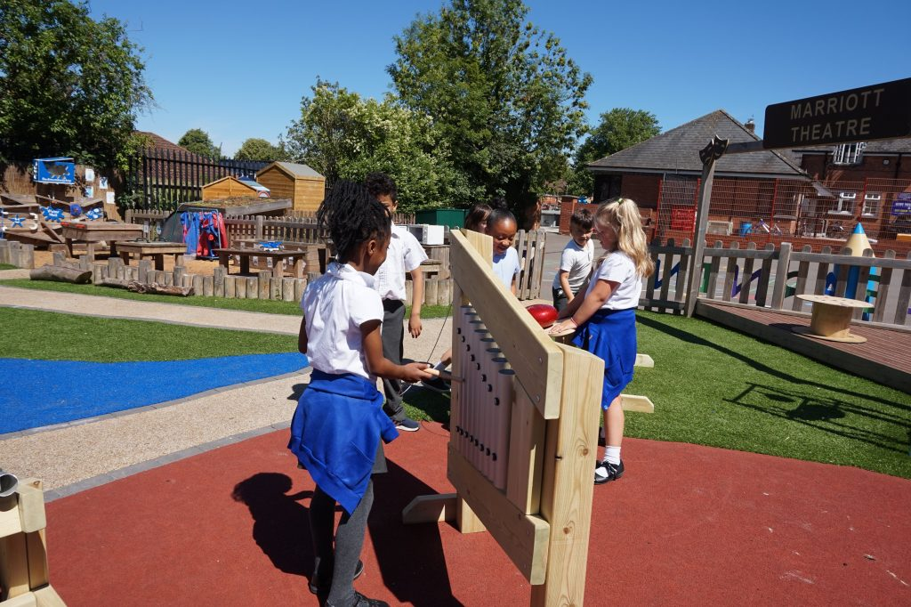 students playing in playground with wooden school playground equipment